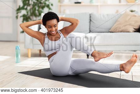 Young Black Woman Exercising In Her House Gym, Doing Abs Exercises, Working Out At Home During Coron