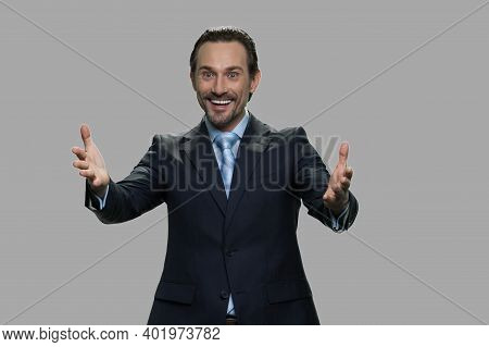 Happy Excited Businessman On Gray Background. Attractive Mature Businessman Raising His Hands In Exc