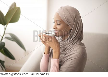 Lovely Black Lady In Traditional Hijab Smelling Coffee, Enjoying Magical Aroma With Closed Eyes, Ind