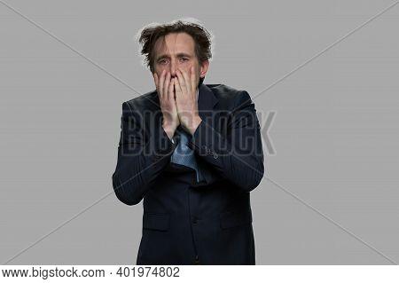 Shocked Desperate Businessman Covering His Face. Stressed Overhelmed Man In Suit Against Gray Backgr