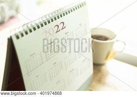 Desktop Calendar 2022 With Tea Cup On Wooden Desk In Private Office