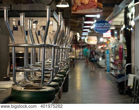 Philadelphia, Usa - June 11, 2019: A Series Of Bar Stools Stacked On The Counter Of A Closed Establi