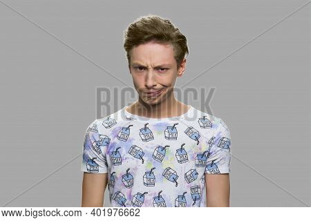 Teen Boy Making Silly Grimace. Funny Teenage Guy Grimacing On Gray Background.