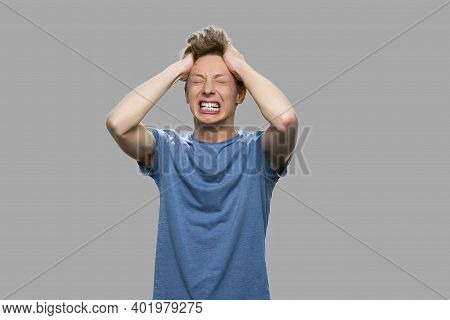 Desperate Teenage Boy On Gray Background. Stressed Furious Teen Boy Shouting And Pulling His Hair. N