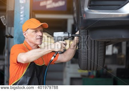 Mechanic Servicing Car Tire With Impact Gun In Garage Of Repair Service Station