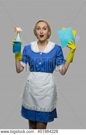 Happy Shocked Maid In Uniform Holding Rags And Detergent. Young Cleaner Maid Woman Holding Cleaning