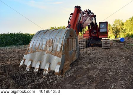 Excavator On Earthwork During Construction Natural Gas Pipeline. Installation Of Gas And Crude Oil P