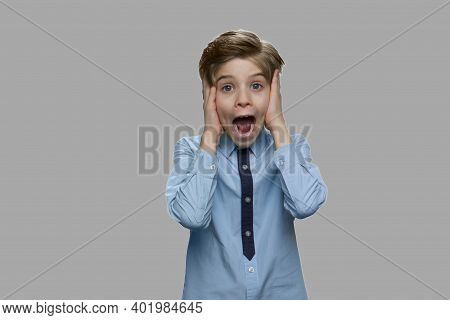 Portrait Of Frightened Child Boy. Shocked Scared Little Boy Screaming Against Gray Background. Human