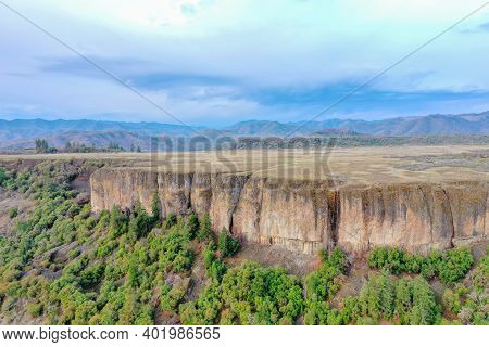 Escarpment Under A Cloudy Sky And Above Pine Trees And Shrubland