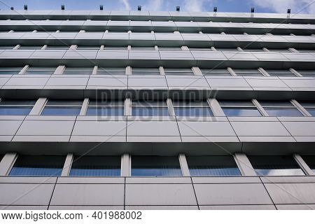 A View From Below On An Office Building In A Business District Against A Blue Sky. Business Building