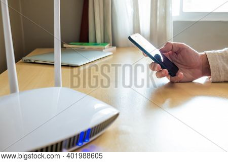 Men Hand Using Smartphone Device To Connect To Wifi Network From Internet Router. Broadband High Spe
