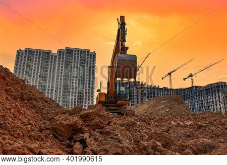 Excavator During Earthmoving Work At Construction Site On Sunset Background. Backhoe Digging Ground