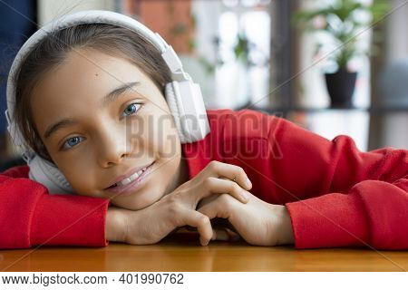 A Blue-eyed Girl With Headphones Listens To Music, Smiles And Looks At The Camera. Modern Technology