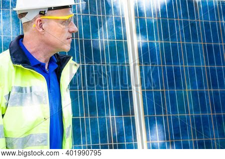 Outdoor Shot Of Caucasian Engineer Inspect Electrical Solar Panel Wearing Hardhat , Protective Eyegl