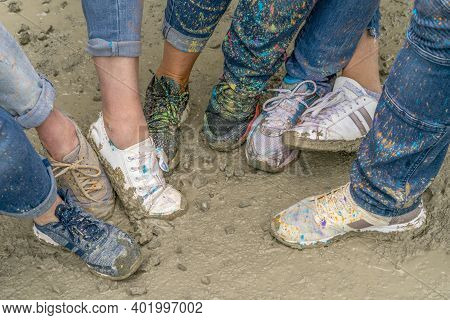 Shoes Spotted With Colorful Paint Splatters On Muddy Ground