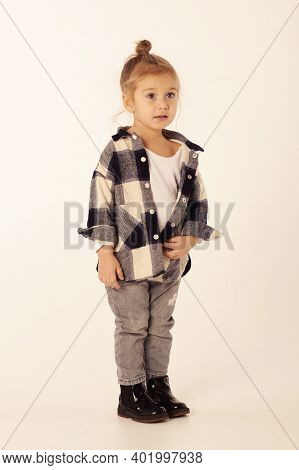Cute Little Blond Baby Girl In Black Boots, Jeans, Checkered Shirt With Copy Space