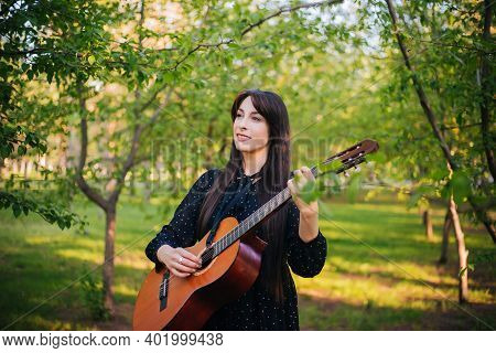 A Woman Is Standing In The Park Among The Trees With An Acoustic Guitar. Girl Musician Is Resting An