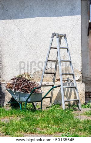Metal Ladder And A Wheelbarrow By The Old Wall