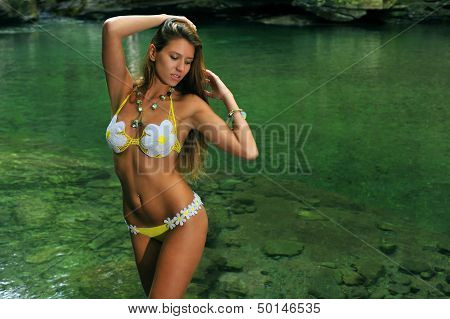 Sexy young woman posing in designer bikini at exotic location of mountain river with green water rocks and forest in background poster
