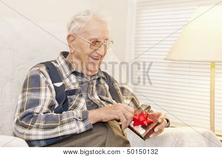 Elderly Man Opening Gift