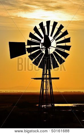 Landscape with windmill water pump at sunrise poster