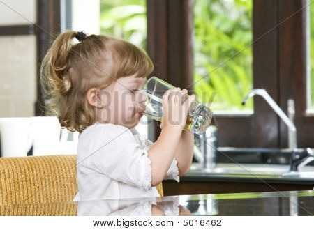 Portrait of little girl having drink in domestic environment poster