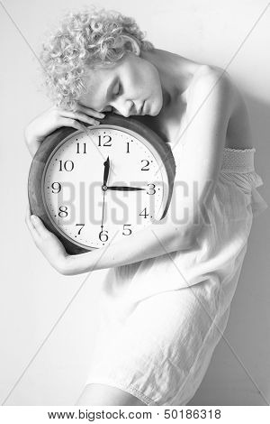 Conceptual portrait of girl in bed with big clock, black and white photo.