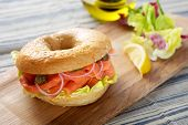 Delicious Salmon Bagel Sandwich on cutting board poster