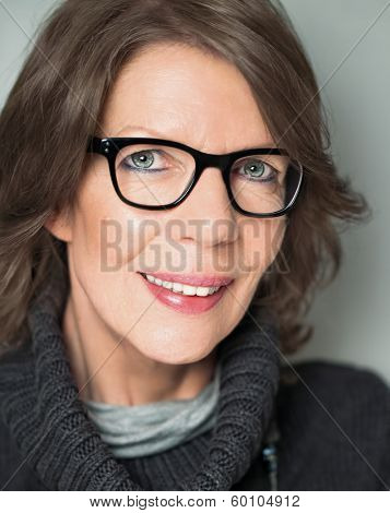 Mature lady with eyeglasses looking relaxed at camera