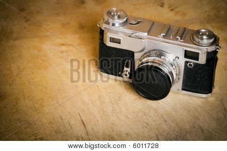 Vintage photo camera on aged wooden background.