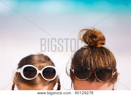 Close up of mother and daughter on summer beach vacation