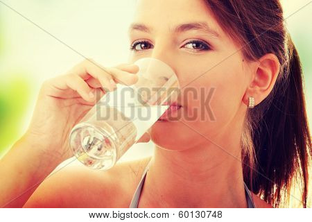Young woman drinking fresh cold water from glass