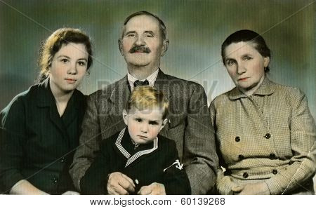 CEGLED, HUNGARY - CIRCA 1977: An antique photo shows hand painted portrait of a family - grandparents, their daughter and grandson
