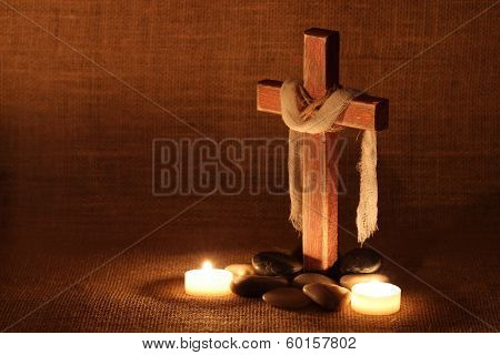 Wooden cross by candlelight and stones with shabby background