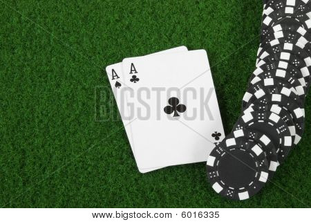 Black poker chips with two aces