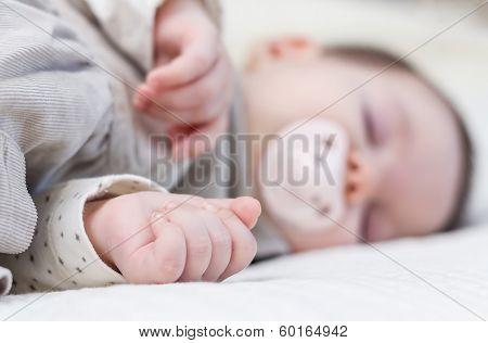 Cute baby girl sleeping over white bedcover