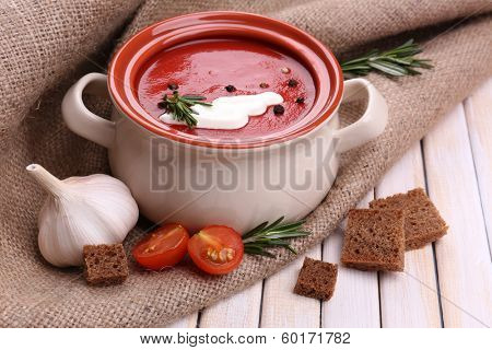Tasty tomato soup on wooden table poster
