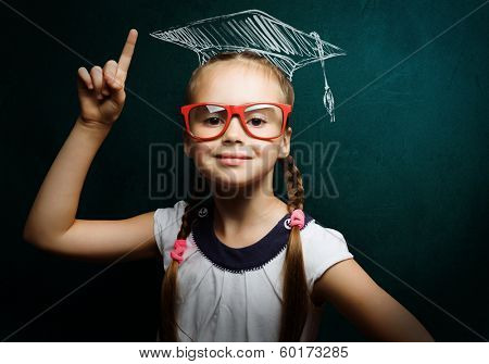 Genius girl in red glasses near blackboard in master hat