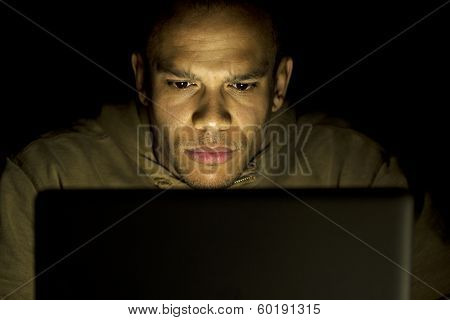A man concentrating whilst using his laptop at night poster