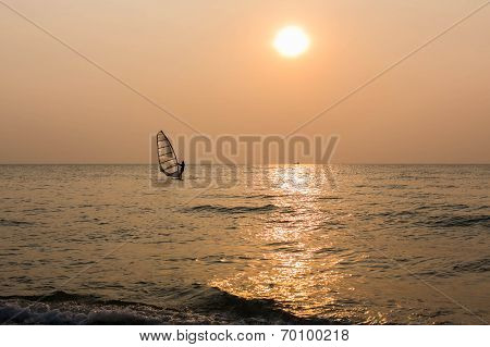 Windsurfer Silhouette In Front Of Sunset Background