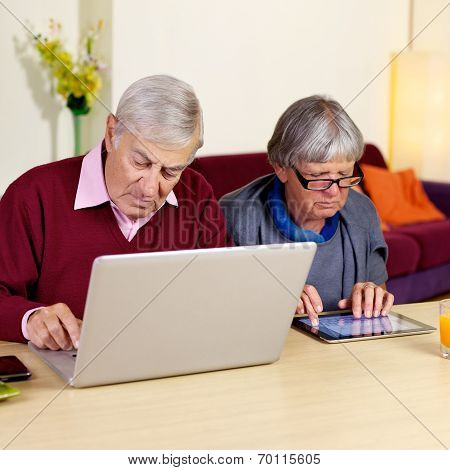 Senior Retired Couple At Home Working On Pad And Pc