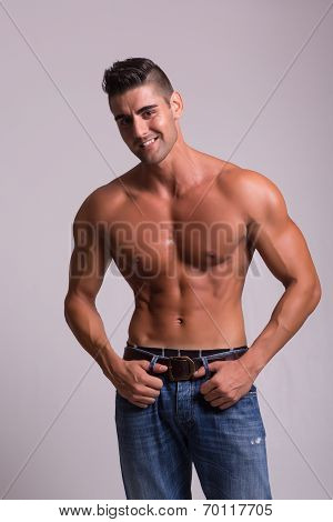 Handsome bodybuilder with a great body posing over a copy space background poster