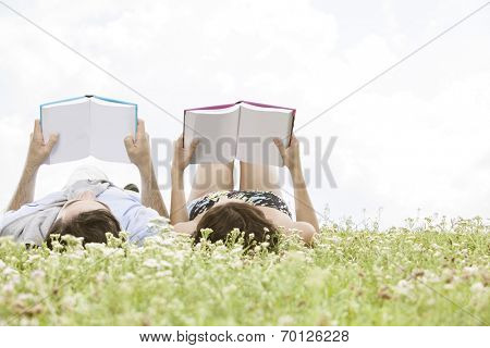 Relaxed young couple reading books while lying on grass against sky