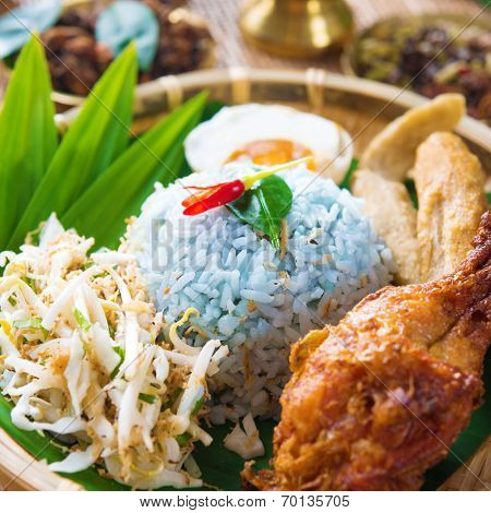 Nasi kerabu or nasi ulam, popular Malay rice dish. Blue color of rice resulting from the petals of butterfly-pea flowers. Traditional Malaysian food, Asian cuisine.