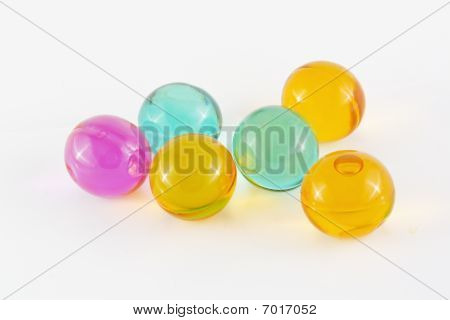 Coloured bath pearls over white background