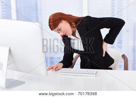 Businesswoman Suffering From Backache At Computer Desk