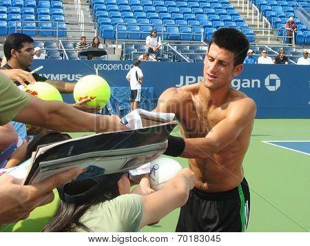 Professional tennis player Novak Djokovic signing autographs after practice