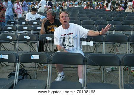 NEW YORK - JUNE 25: An unidentified man gestures as he prays on the second night of the Billy Graham Crusade at Flushing Meadows Corona Park on June 25, 2005 in Flushing, New York.