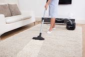 Cropped image of young maid cleaning carpet with vacuum cleaner at home poster