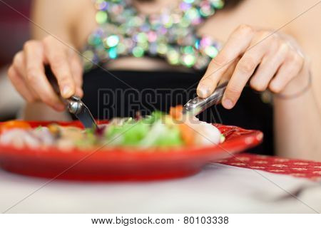 Woman eating in a restaurant closeup